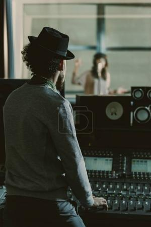 handsome sound producer in hat recording song at studio