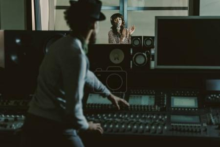 Photo for Sound producer in hat recording song at dark studio - Royalty Free Image