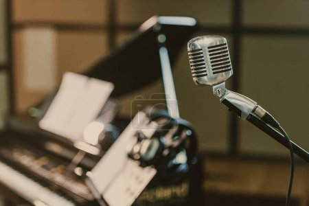 close-up shot of vintage microphone in front of blurred piano