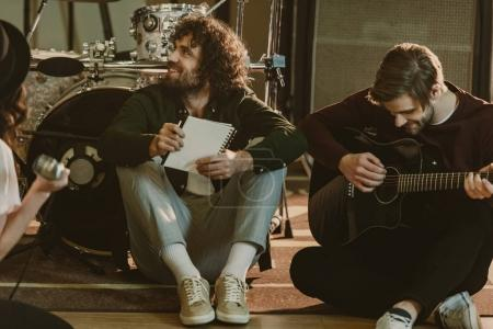 young music band sitting on floor with notepads and talking