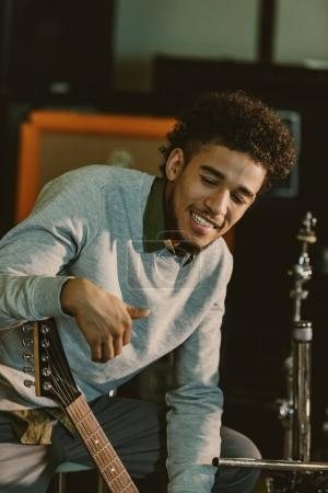 handsome happy musician with electric guitar at studio