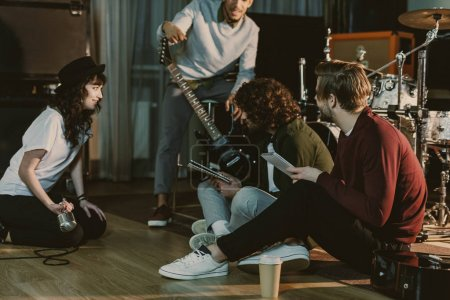 music band sitting on floor and creating text for song together