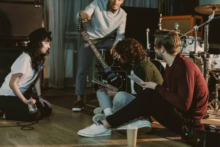 Photo pour Groupe de musique assis sur le sol et la création de texte pour la chanson ensemble - image libre de droit