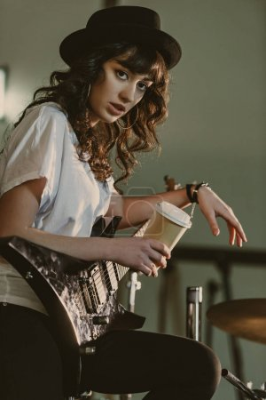Photo for Beautiful female musician with electric guitar and cup of coffee to go looking at camera - Royalty Free Image
