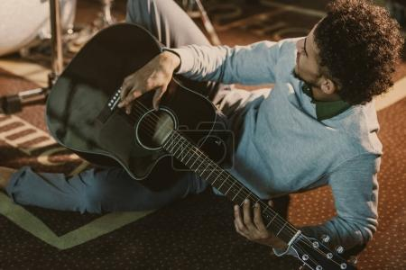 handsome african american man lying on floor of studio with acoustic guitar
