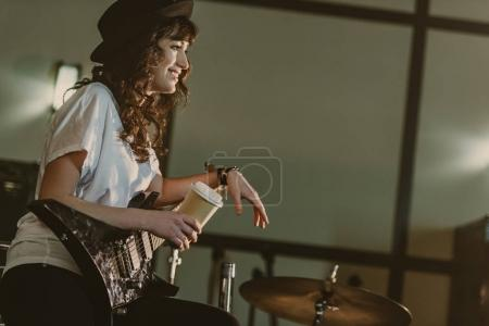 beautiful female musician with electric guitar and cup of coffee to go