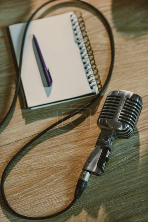 top view of wired retro microphone lying on wooden table with blank notebook