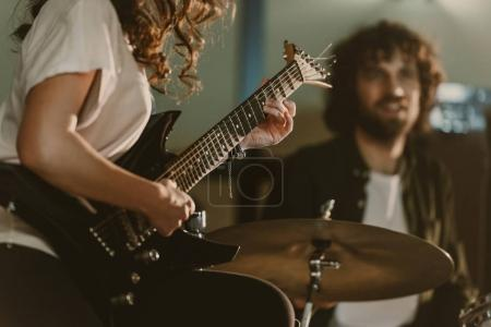 cropped shot of female guitarist performing song with blurred drummer on background