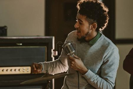 Photo for Handsome african american singer performing song with microphone - Royalty Free Image