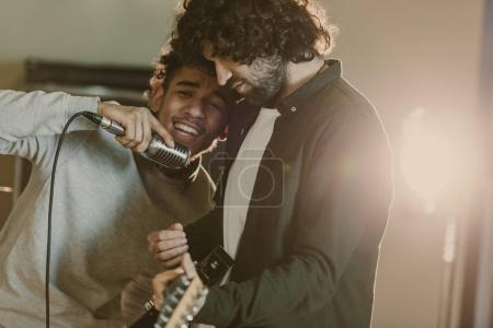Photo for Young emotional singer performing song near guitarist - Royalty Free Image