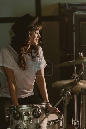 beautiful female drummer sitting at drum set