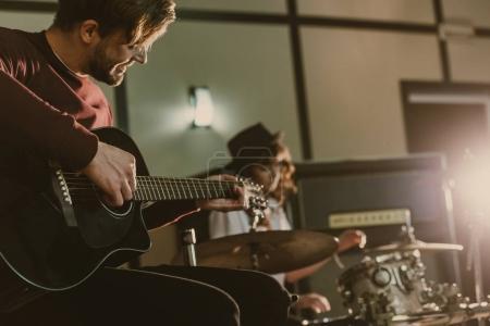 Photo pour Beau jeune musicien jouer de la guitare sur la répétition avec le batteur de femme floue derrière - image libre de droit