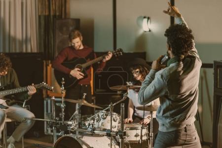 Photo pour Groupe de musique rock jouant ensemble au studio - image libre de droit