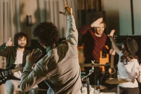 Photo for Singer stretching hand to happy music band while they having repetition - Royalty Free Image