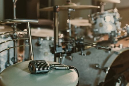 vintage microphone lying on chair in front of drum set