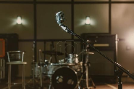 Photo for Vintage microphone on stand against blurred drum set - Royalty Free Image