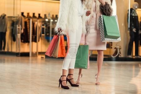 Photo pour Section basse de femmes multiethniques à la mode en manteaux de fourrure tenant des sacs en papier et faisant du shopping ensemble dans un centre commercial - image libre de droit
