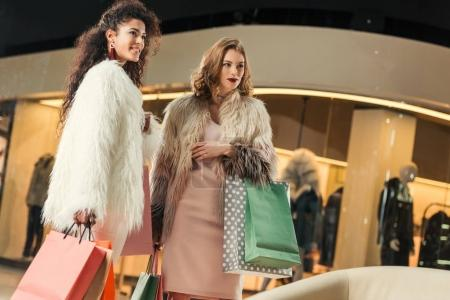 Photo pour Belles jeunes femmes multiethniques dans des manteaux de fourrure trendy portant des sacs de papier lors de vos achats ensemble au centre commercial - image libre de droit