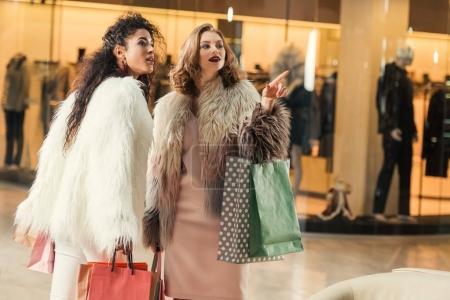Photo pour À la mode femmes multiethniques tenant des sacs en papier et en pointant avec le doigt au centre commercial - image libre de droit