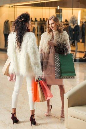 Photo pour La mode jeunes femmes multiethniques de manteaux de fourrure, portant des sacs de papier lors de vos achats ensemble au centre commercial - image libre de droit
