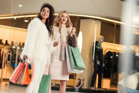 Foto de Con estilo jóvenes multiétnicas en abrigos de piel con bolsas de papel al ir de compras juntos en el centro comercial - Imagen libre de derechos