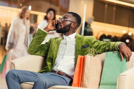 Photo pour Bel homme africain-américain parlant de smartphone tout en se reposant avec des sacs de shopping au centre commercial - image libre de droit