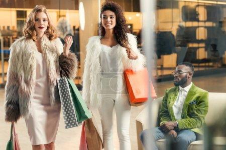 Photo pour Élégantes jeunes femmes multiethniques avec sacs à provisions marche et afro-américain assis derrière dans centre commercial - image libre de droit