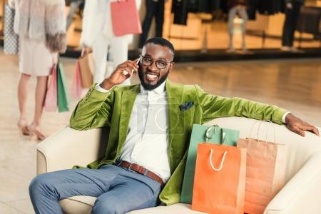 handsome stylish african american man talking by smartphone while sitting with shopping bags in mall