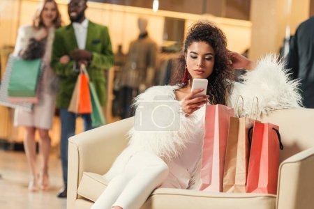 Foto de Joven moda mujer afroamericana con smartphone sentado con bolsas de compras en centro comercial - Imagen libre de derechos