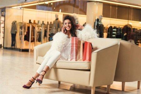 Foto de Hermosa mujer afroamericana sonriente, hablando por teléfono inteligente sentado con bolsas de compras en centro comercial - Imagen libre de derechos