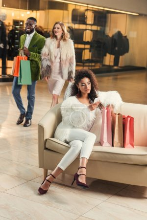 Photo pour Jeune femme à l'aide de smartphone tout en se reposant avec des sacs à provisions et élégant couple marchant derrière dans centre commercial - image libre de droit