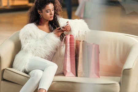 young stylish african american woman using smartphone while sitting with shopping bags in mall