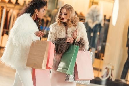Photo pour Femmes multiethniques à la mode dans les manteaux de fourrure, tenant les sacs en papier et shopping ensemble au centre commercial - image libre de droit