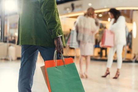 cropped shot of african american man holding paper bags while walking in shopping mall