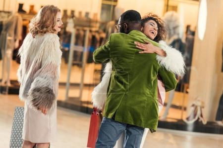 Photo pour À la mode jeune couple afro-américain étreindre lors de vos achats au centre commercial - image libre de droit