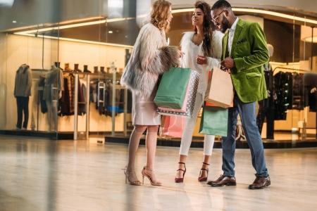 Photo pour Vue sur toute la longueur heureux peuple multiethnique élégant à la recherche dans des sacs de shopping au centre commercial - image libre de droit