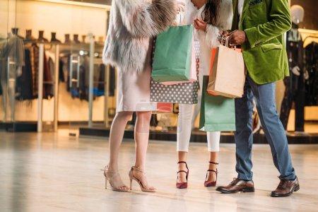 Photo pour Recadrée tir d'élégant personnes multiethnique se tenant les sacs en papier au centre commercial - image libre de droit