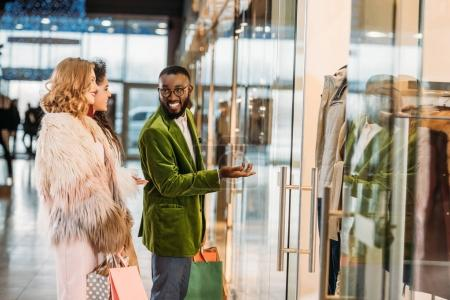 side view of smiling stylish multiethnic people shopping together in mall