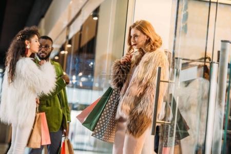 Photo pour Jeune femme avec des sacs à provisions à la recherche de suite alors qu'il se couple afro-américain derrière - image libre de droit