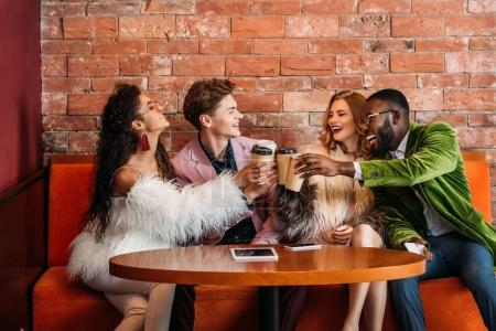smiling trendy multiethnic young friends drinking coffee from paper cups