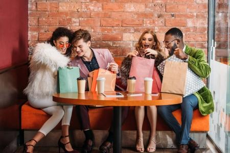 smiling trendy multiethnic young people looking into paper bags while drinking coffee together
