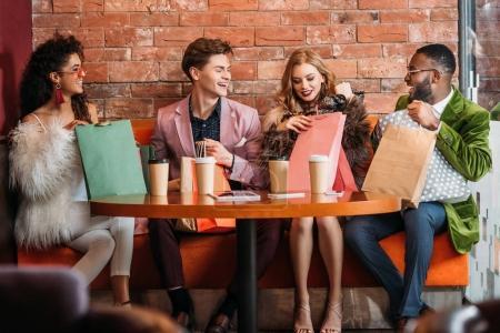 Foto de Moda jóvenes multiétnicos busca en bolsas de papel mientras toman café juntos - Imagen libre de derechos