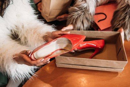 Photo pour Recadrée tir des filles dans des manteaux de fourrure trendy tenue boîte avec élégantes chaussures à talon haut - image libre de droit
