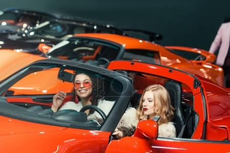 fashionable smiling multiethnic women sitting in luxury red car