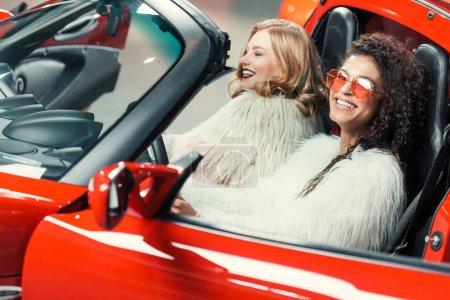 Photo pour Heureux élégantes femmes multiethniques en manteaux de fourrure, assis dans la voiture de luxe rouge - image libre de droit