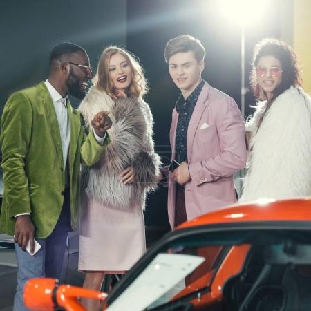 Photo pour Chic jeunes multiethnique en regardant la voiture rouge moderne - image libre de droit