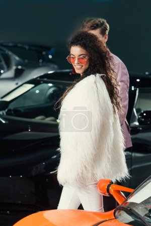 young couple choosing new car at showroom