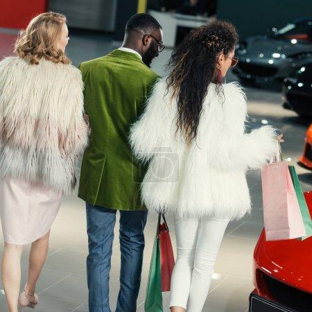 Photo pour Acheteurs jeunes élégants marche par salle d'exposition auto - image libre de droit