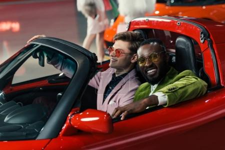 smiling stylish multiethnic men sitting in new car at showroom