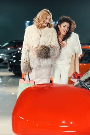 Photo pour Jeunes femmes en manteaux de fourrure, regardant les voitures dans la salle d'exposition - image libre de droit